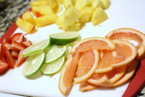 Prep the fruit by slicing the ½ grapefruit, 1 lime, and 1 peach into thin slices.  Remove the hull from the strawberries, and cut into slices.  Cut the pineapple into chunks.