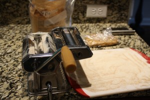"""I usually set up a little """"station"""" for my pasta rolling.  I lightly flour a cutting board, and set it on the end where the pasta comes out.  I keep extra flour handy for dusting the pasta, cutting board, my hands, and machine.  I also like to keep some plastic wrap around.  You'll want to keep the pasta covered, so it doesn't dry out too much."""