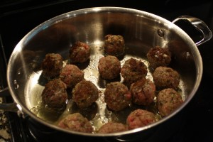 When meatballs are ready to turn, they should be easy to turn.  They may not be ready all at once.  You'll want a nice caramelization color on them.