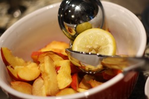 Place the sliced peaches into a large mixing bowl and sprinkle with the juice of ½ a lemon.  Toss to combine.