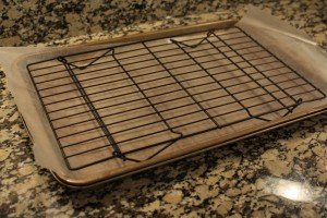 Lay a sheet of waxed paper onto a baking sheet.  Place a wire cooling rack on top of the waxed paper.