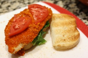 Place a leaf of lettuce on one slice of toasted bread, then a Buffalo wing sauce-smothered chicken cutlet, then a slice of tomato cut in half.