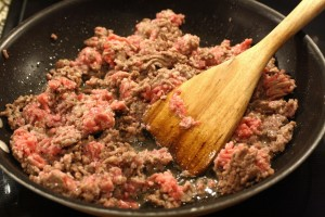 As the beef and sausage cook, give it a little mash to break up into chunks.