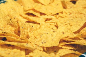 Layer tortilla chips onto a foil covered baking sheet.  The size of baking sheet I used is a 15.25 inch x 10.25 inch x .75 inch.