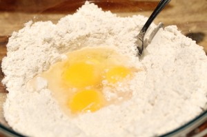 Put flour into a mixing bowl.  Create a little well in the middle.  Add the yolks, egg, and water into the well.