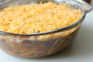 Top the chili casserole with the shredded cheddar cheese.
