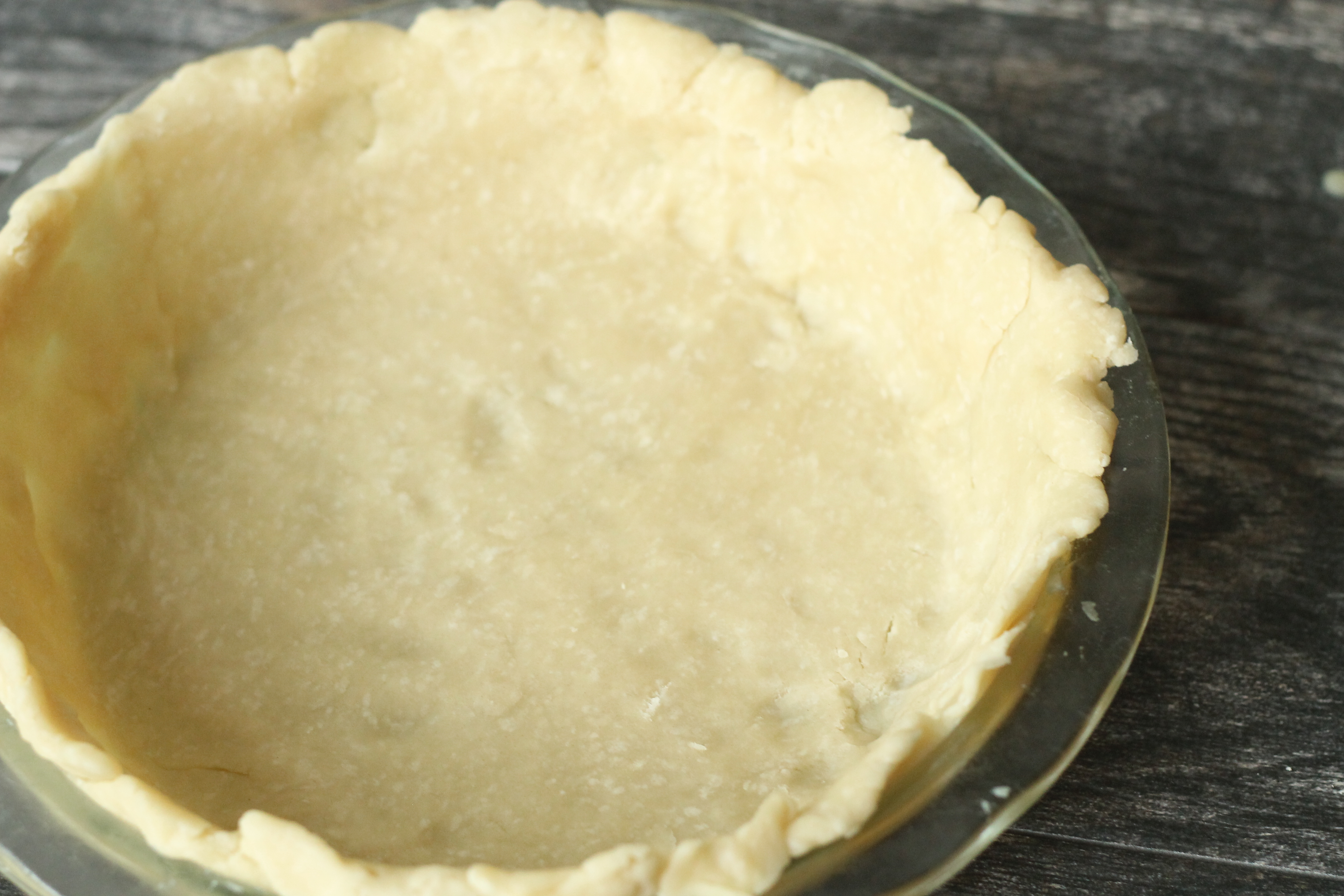 In a greased pie pan, lay in the first sheet of pie dough. Trim any ...