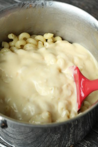 pour cheese sauce into macaroni